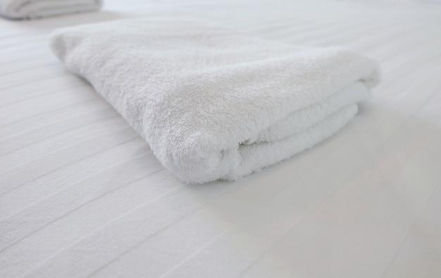 Weißes handtuch auf weißem bett im schlafzimmer