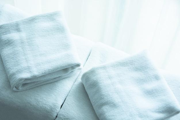 Weißes handtuch auf weißem matratzenstoff, morgens weiches licht.