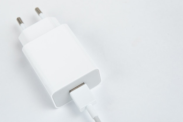 Weißes handy-ladegerät auf dem weißen isolierten hintergrund - mit usb-kabel