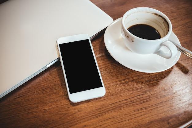 Weißes handy mit leerem schwarzen desktop-bildschirm auf einem computer-laptop mit kaffeetasse