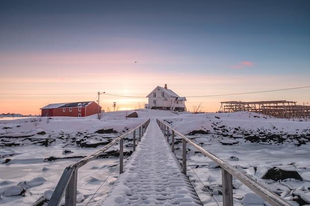 Weißes haus mit holzbrücke und gefrorener küstenlinie