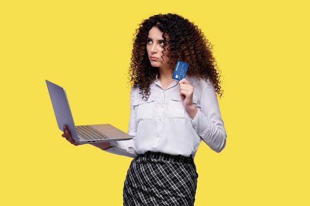 Weißes hemd der geschäftsfrau macht einkäufe in einem online-shop unter verwendung des laptops und hält bankkarte in ihren händen auf gelbem lokalisiertem hintergrund