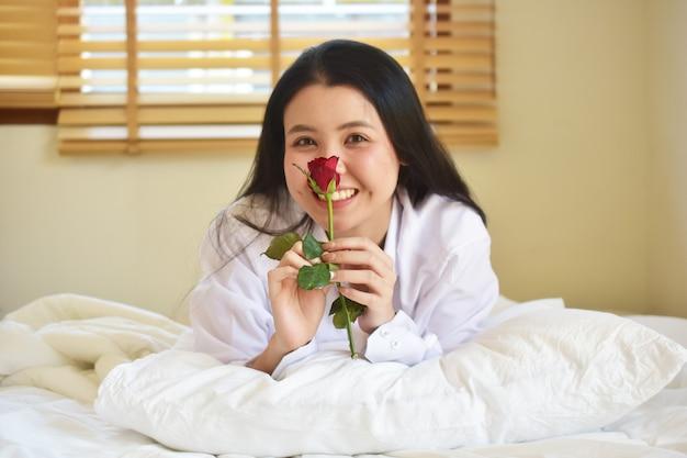 Weißes hemd der schönheitsfrauen mit stieg ist auf bettraum, reizendes lächeln der jungen frauen in konzept liebe valentinstag