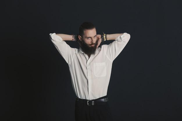 Weißes hemd des bärtigen mannes der hippie-art im studio über schwarzem hintergrund