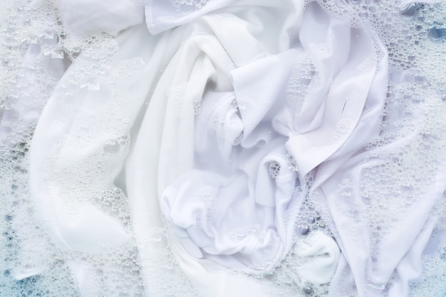 Weißes hemd in pulver waschmittel wasserlösung einweichen. wäscherei-konzept