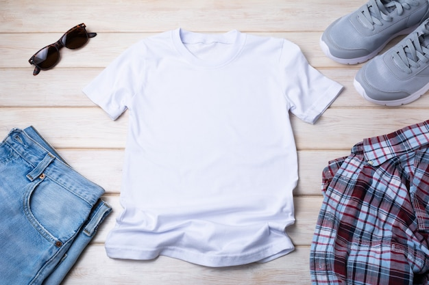 Weißes herren-baumwoll-t-shirt-modell mit sonnenbrille, grauen laufschuhen, blue jeans und kariertem hemd. design-t-shirt-vorlage, t-shirt-druck-präsentationsmodell