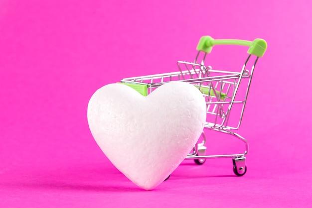 Weißes herz neben einem einkaufskorb auf einem rosa raum. liebe kaufen, herz kaufen.