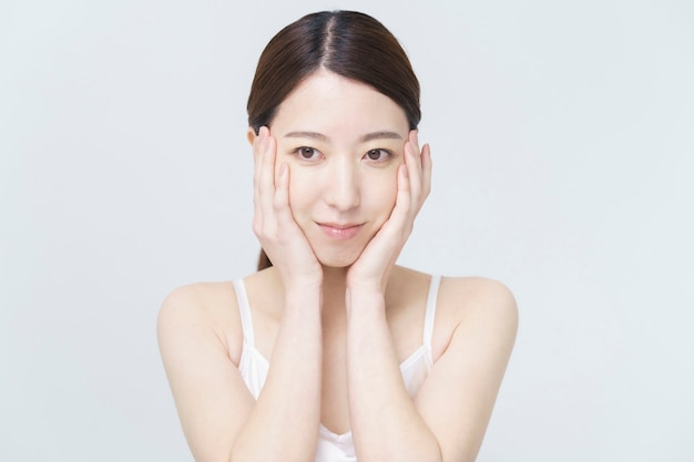 Weißes hintergrundschönheitsbild / asiatische frau, die ihr gesicht berührt