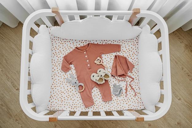 Weißes hölzernes babybett mit kissenförmigen wolken im babyzimmer. neugeborene kleidung und accessoires im kinderbett. draufsicht auf das kinderbett