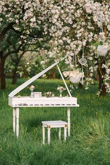Weißes hölzernes klavier mit schemel und romantischem dekor umgeben durch blühenden garten der apfelbäume im frühjahr