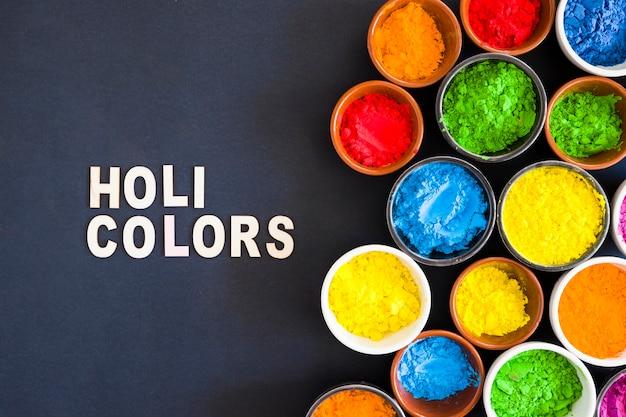 Weißes holi färbt text nahe dem holi farbpulver in der schüssel gegen schwarzen hintergrund