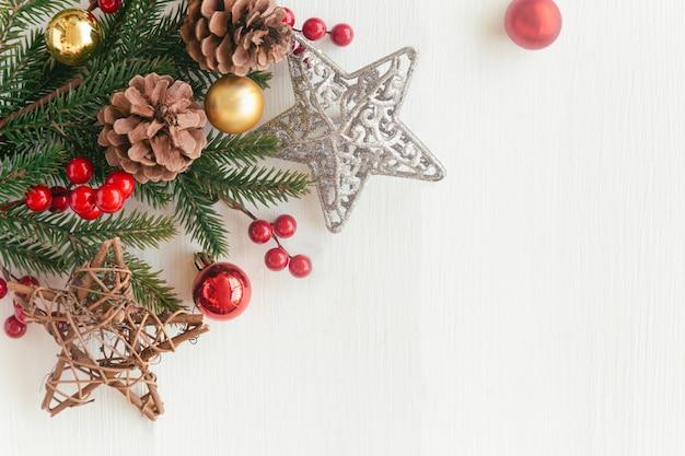 Weißes holz mit kiefernblatt, kiefernkegeln oder nadelbaumkegel, stechpalmenbällen, stern, zuckerstange und flitter im weihnachtskonzept. hölzerner plankenhintergrund in der draufsichtebenenlage mit kopienraum für weihnachtstapete