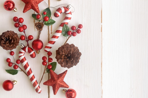 Weißes holz mit kiefernkegeln oder nadelbaumkegel, roten stechpalmenbällen, funkelnstern, zuckerstange und flitter im weihnachtskonzept schöner plankenhintergrund im draufsichtebenenlage-kopienraum für weihnachtstapete
