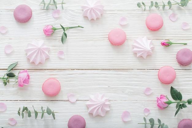 Weißes holz mit rosa blumen, makronen und blättern hintergrund