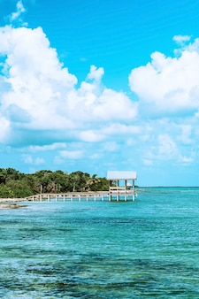 Weißes holzdock auf blauem meer unter blauem und weißem bewölktem himmel während des tages