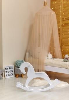Weißes holzpferd im niedlichen kinderzimmerinnenraum mit spielzeug und modernen möbeln, bett mit zelt