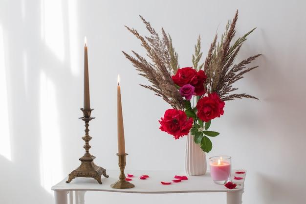 Weißes interieur mit rosenstrauß und brennenden kerzen