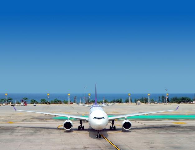 Weißes jet-flugzeug auf der rollbahn an einem sonnigen tag auf hintergrund des blauen himmels