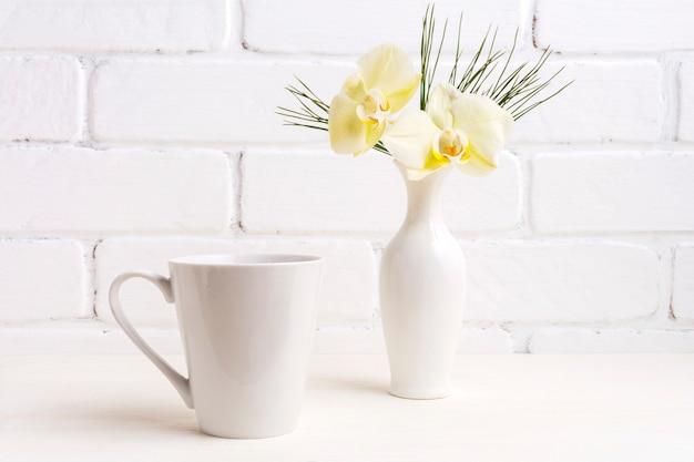 Weißes kaffee-latte-becher-modell mit sanfter gelber orchidee in der vase