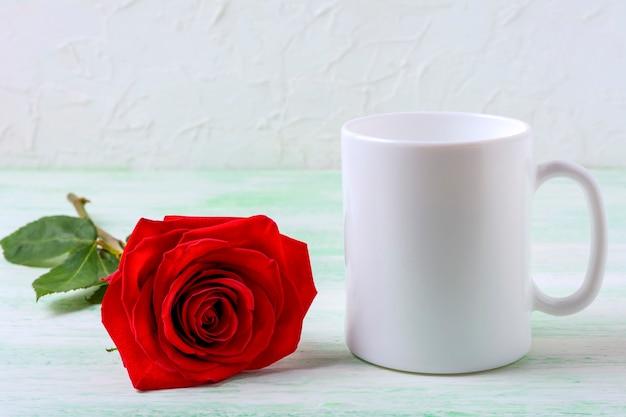 Weißes kaffeetassenmodell mit sinnlicher dunkelroter rose
