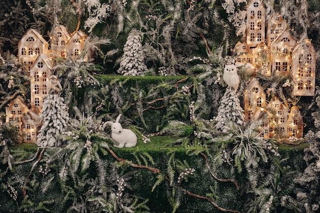Weißes kaninchen sitzt links von der ausgestopften eule mit leuchtenden puppenhäusern