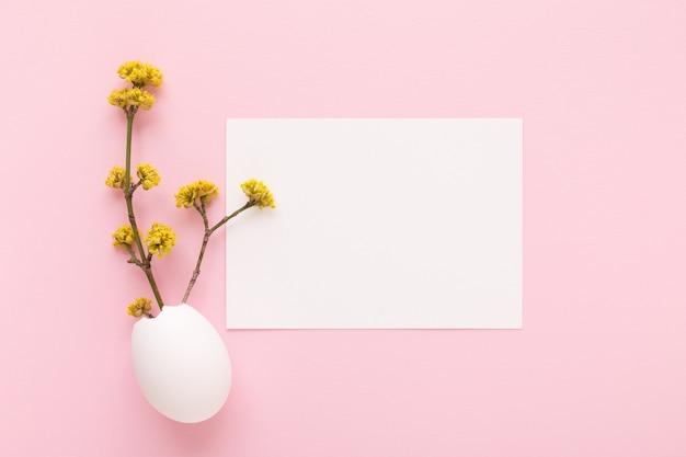 Weißes kartenmodell und blühender zweig innerhalb der ostereierschale auf rosa hintergrund. ostertagsgrußkarte.
