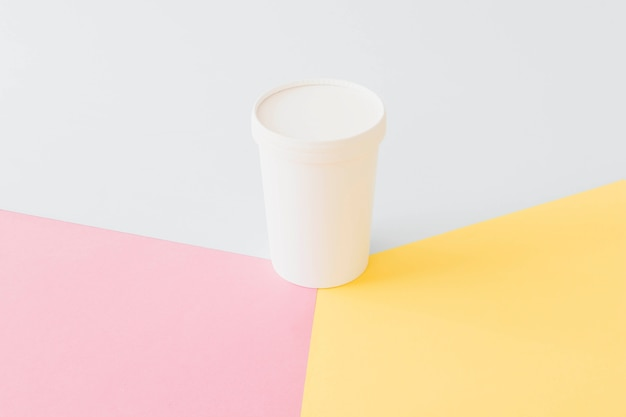 Weißes kartonglas auf hellem brett