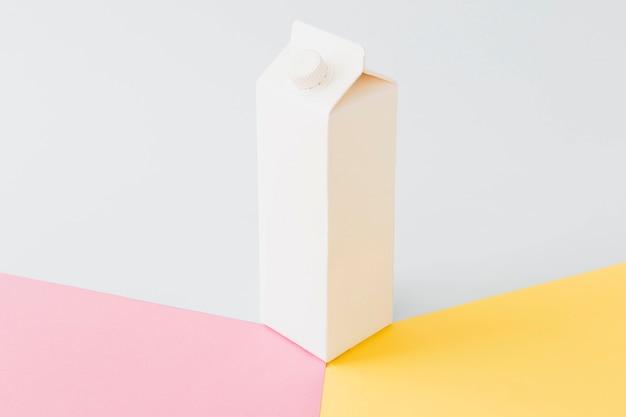 Weißes kartonmilchpaket auf hellem brett