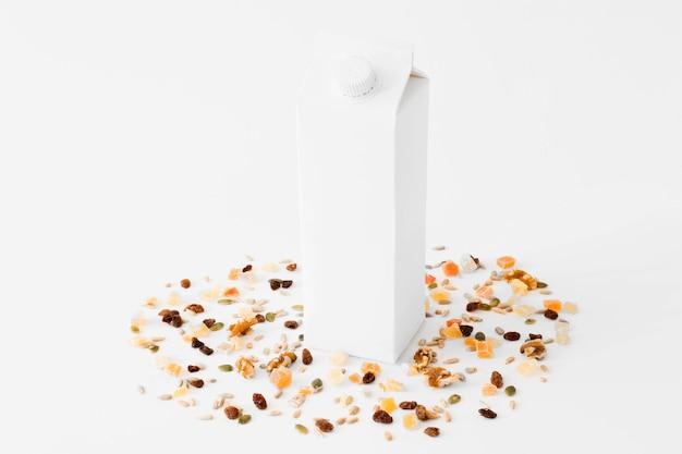 Weißes kartonmilchpaket zwischen getrockneten früchten und nüssen