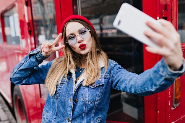 Weißes kaukasisches mädchen, das telefon für selfie verwendet, während kussgesichtsausdruck macht. outdoor-dame in jeansjacke und rotem hut steht auf der straße und macht ein foto von sich.