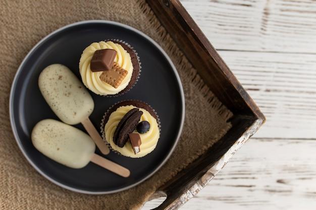 Weißes kekseis am stiel und leckere muffins und cupcakes auf einem tablett auf einem holztisch. dekoriert mit verschiedenen bonbons, keksen und farbigem süßem frischkäse.