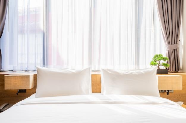 Weißes kissen auf bettdekoration mit heller lampe und grünem baum in den blumentöpfen im hotelschlafzimmer