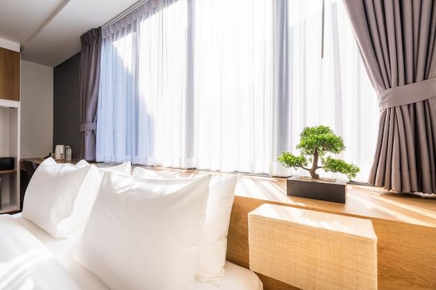 Weißes kissen auf bettdekoration mit heller lampe und grünem baum in den blumentöpfen