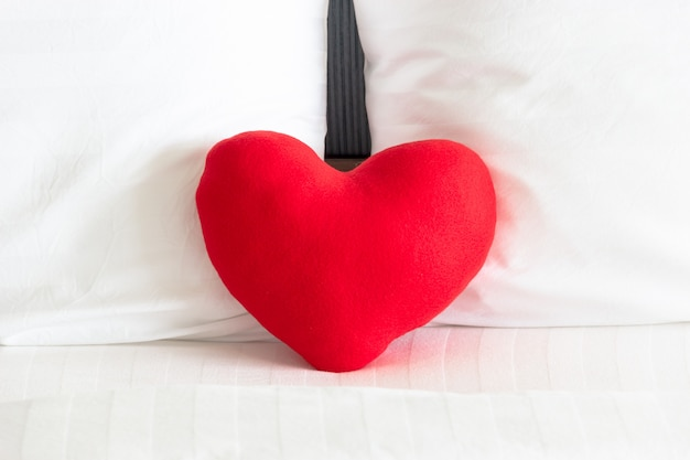 Weißes kissen des roten herzens und der paare auf dem bett für liebes-, hochzeits- und valentinstagkonzept