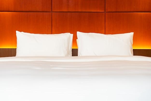 Weißes kissen und decke auf bett mit lichtlampendekoration des innenraums des schlafzimmers