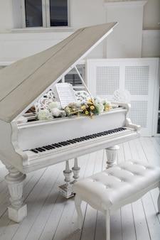 Weißes klavier im weißen raum