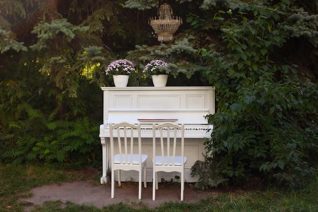 Weißes klavier und stühle mit romantischem dekor im sommer im garten. dekor für eine hochzeit oder ein romantisches abendessen. der mit blumen geschmückte flügel steht im freien. gartendekoration. rustikal. feier
