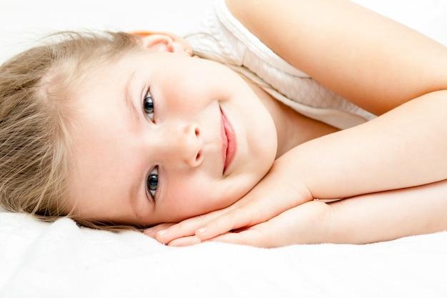 Weißes kleid des recht kleinen blonden mädchensommers, das auf dem boden liegt und an der kamera auf weiß lächelt