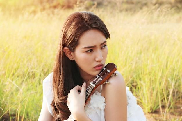 Weißes kleid schönen asien-mädchens, das auf einer ukulele spielt