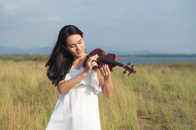 Weißes kleid schönen asien-mädchens, das auf einer violine spielt
