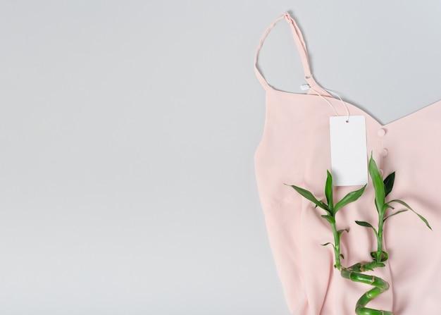 Weißes kleidungsetikett, leere mockup-vorlage beschriften. auf einem hochwertigen baumwoll-rosa-blusenstoff-textil