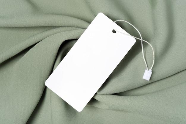 Weißes kleidungsetikett, leere mockup-vorlage beschriften. auf einem hochwertigen baumwollgrünen khaki-stoff-textil