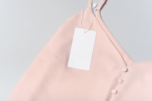 Weißes kleidungsetikett, leere mockup-vorlage beschriften. auf einer hochwertigen rosa baumwollbluse auf grauem hintergrund