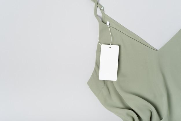 Weißes kleidungsetikett, leere mockup-vorlage beschriften. auf einer khakigrünen bluse aus hochwertiger baumwolle auf grau