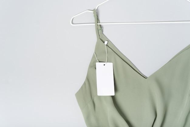 Weißes kleidungsetikett, leere mockup-vorlage beschriften. auf einer khakigrünen bluse aus hochwertiger baumwolle. aufhänger