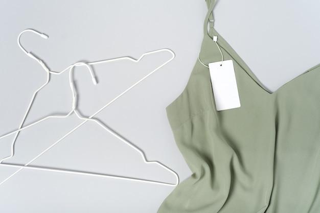 Weißes kleidungsetikett, leere mockup-vorlage beschriften. auf einer khakigrünen bluse aus hochwertiger baumwolle, kleiderbügel