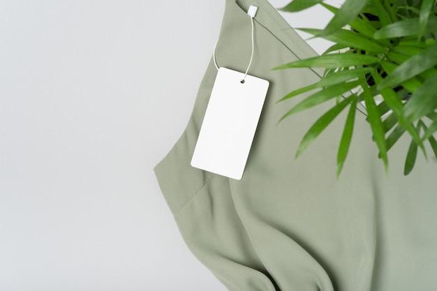 Weißes kleidungsetikett, leere mockup-vorlage beschriften. auf einer khakigrünen bluse aus hochwertiger baumwolle