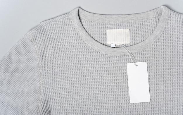 Weißes kleidungsetikett, leere mockup-vorlage beschriften. herren warmer pullover für männer baumwolle auf grauem hintergrund