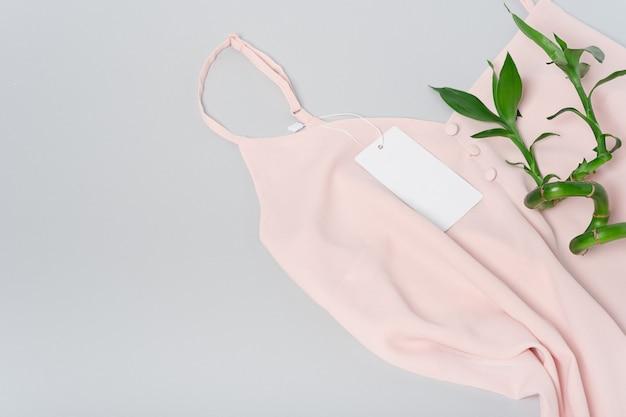 Weißes kleidungsetikett, leere mockup-vorlage beschriften. premium baumwolle rosa bluse stoff textil. bambus