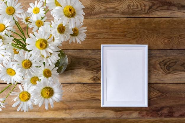 Weißes kleines rahmenmodell mit gänseblümchen-wildblumen